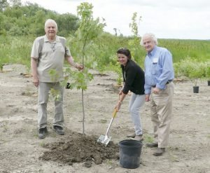 Planting a tree on the levelled-out area excavated from the river are, from left, Bill Smirle, Susan LeClair and Pat Sayeau. Zandbergen photo, Nation Valley News