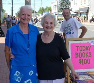 Embracing the Arts at Dairyfest Shirley Fawcett has seen a few Dairyfests come and go from the Main St., Winchester, shop where she's worked behind the counter since 1949. She poses here Aug. 6 with daughter Julie McKay, while Rob Fawcett looks on from behind the book sale sign at Embracing the Arts. The proprietor reported steady sales at the special $1-per-price applicable that week. Zandbergen photo, Nation Valley News
