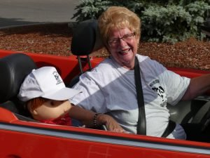 Ragtop Jan Clapp enjoyed Dairyfest aboard her convertible with accompanying mascot. Zandbergen photo, Nation Valley News