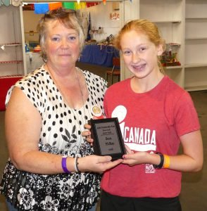 Seca McRae (right) receives her Senior Youth homecraft plaque, after topping the standings in the age 12 to 16 class. Zandbergen photo, Nation Valley News