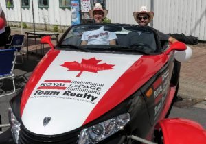 Prowler Clayton Oldford (left) and Nathan Lang, sales representatives with the Oldford Team realty operation, took some shade under straw hats while posing in the Royal LePage Prowler.