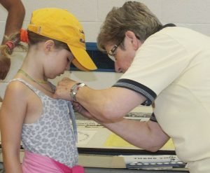 Rotarian Betty Vanden Bosch affixes a ribbon on Skye Dixon, 8, member of the Dixon Team who have been stalwart supporters of the North Dundas Terry Fox Run each year. Zandbergen photo, Nation Valley News