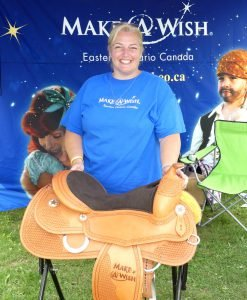 Janet-Lee Ferris, Manager of Fund Development for Make-A-Wish Eastern Ontario, poses with the $3,000 reining saddle that was raffled off at the weekend symposium. Proceeds of the draw for the donated Continental Saddlery piece went to Make-A-Wish Eastern Ontario. A painting by Theresa Reuter was also raffled off for the cause. Zandbergen photo, Nation Valley News