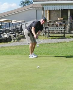 Mountain Fire Chief Raymond Sherrer tries out the putting contest. Zandbergen photo, Nation Valley News