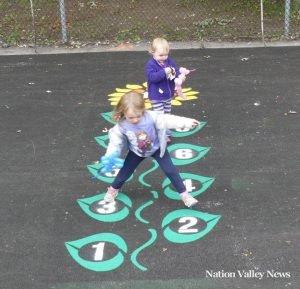 Lauren Scott, 4, and Katherine Scott, 2, enjoy the new hopscotch design at Matilda Memorial Park. Zandbergen photo, Nation Valley News