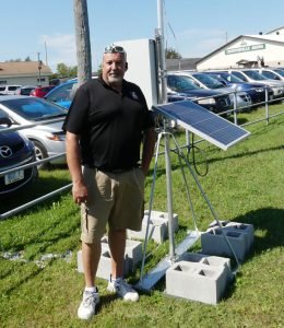 Storm Internet Business Development Associate Peter Vanderlind poses with a piece of new WiFi technology that underwent beta testing during the Chesterville Fair in August — a solar-powered WiFi portable access point. The fairgrounds otherwise featured several conventionally powered access points to provide wireless service to fairgoers. A single conventional unit atop Barkley's Shoes and Accessories in Winchester similarly offers free WiFi to the public in Sweet Corner Park. Zandbergen photo, Nation Valley News.