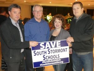 From left, SDG Warden Jamie MacDonald, local MPP Jim McDonell, and Jennifer MacIsaac and Dale Rudderham, at the Nov. 11 Save South Stormont Schools fundraiser event in Long Sault, featuring 'Twisted Kilt' — seen on stage in the background. Zandbergen photo, Nation Valley News
