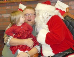 Evelynn Merkley-Barton, 2, was not impressed by her grandfather Glen Merkley accepting a peck on the cheek by Old St. Nick, during the Chesterville Breakfast with Santa, Dec. 3. Zandbergen photo, Nation Valley News