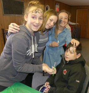 Henry Link, 9,receives some colour from Shannon Harper, 11 (left), Kailey Marshall, 11, and Kate Link-Horvath, 11. Zandbergen photo, Nation Valley News