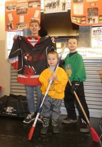 From left, Etienne Bray, 13, Spencer Casselman, 3 and Brady Casselman, 8, pose at the Finch Youth Broomball tournament, in front of a display featuring last November's World Broomball Championships in Saskatchewan — where the men's team won gold with a squad of Eastern Ontarians. The boys in the phoot play broomball at the Bantam/Midget, Sprout and PeeWee level, respectively. Zandbergen photo, Nation Valley News