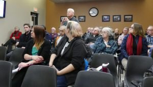 Dr. Gerry Rosenquist poses a question to the consultant after the presentation. The public gallery was almost full —but not packed, either. Zandbergen photo, Nation Valley News